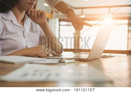 Businesswoman working with businessman. two business people discussing document and idea at meeting. Woman using laptop with her colleague in office. Conference discussion corporate concept