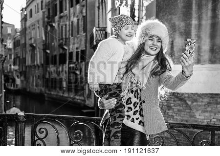 Mother And Child Taking Selfie With Mobile Phone In Venice