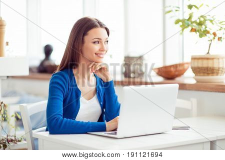 Young Attractive Lady Is Dreamy, Browsing On Her Laptop In The Cafe. She Is In Casual Outfit, Smilin