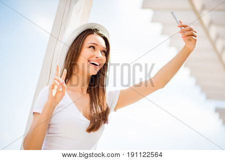 Carefree And Happy, Funky Mood. Low Angle Of Cute Young Girl, Making Selfie On A Camera Of Her Pda I
