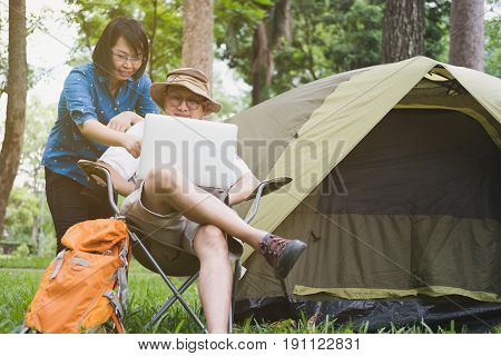 Young Man Tourist Sitting On Chair And Using Laptop With His Couple In Front Of Tent At Camping Site
