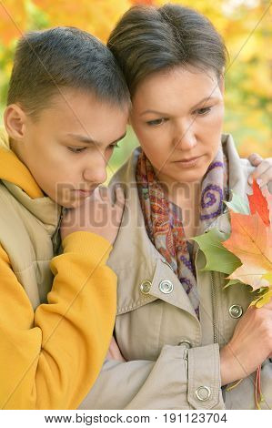 Close up portrait of sad mother and son hugging outdoors