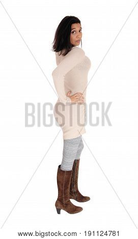 A young Hispanic woman standing in profile in a knitted dress and brown boots isolated for white background.