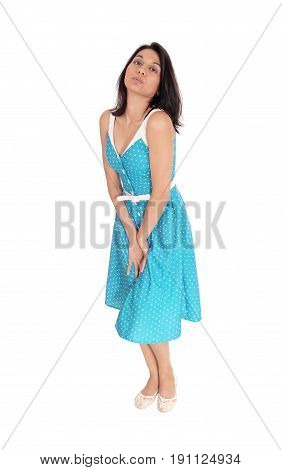 A beautiful woman in a blue dress standing with her hands between her legs need to pee isolated for white background.