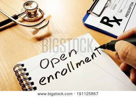 Open enrollment written on a note and medical stethoscope.