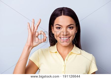 Successful Smiling Latin Mulatto Brunette Girl Is Showing Ok Sign On Light Blue Background. She Has
