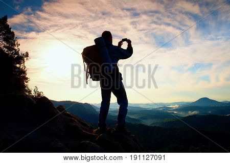 Tourist With Heavy Backpack Takes Photos With Smart Phone. Man On The Rocky Peak. Dreamy Fogy Valley