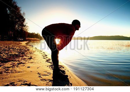Silhouette Of Sport Active Man Running And Exercising On The Beach At Sunset.