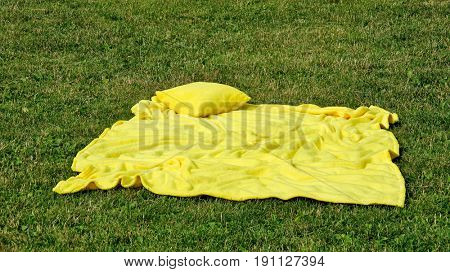 yellow pillow and blanket on the grass