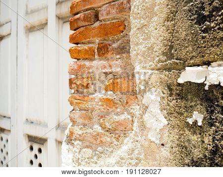 Old wall broken brick see a orange brickwall inside. The side has old gray wooden doors.