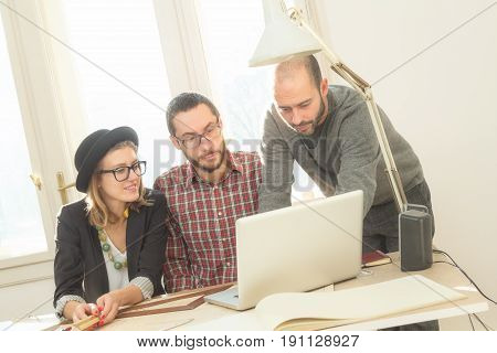 Young group of people discussing business plans with lap-tops plans in a room lit by natural sunlight.