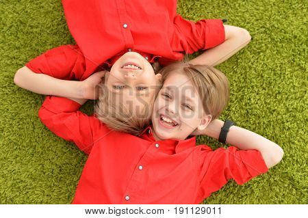 Two smiling boys in red shirts lying on floor with green carpet