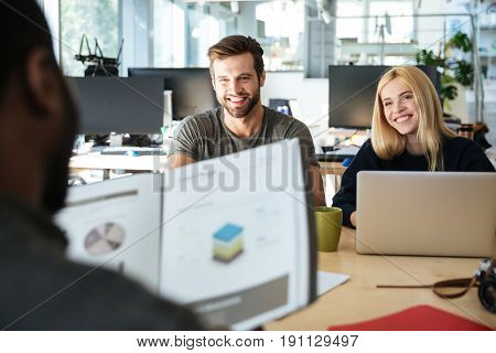 Picture of happy young colleagues sitting in office coworking using laptop computers and holding diagrama. Looking aside.
