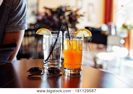 Refreshing glass of ice cold water with cubes and ice-tea arnold palmer drink with tea and lemonade mixed for hot summer day refreshements with straws