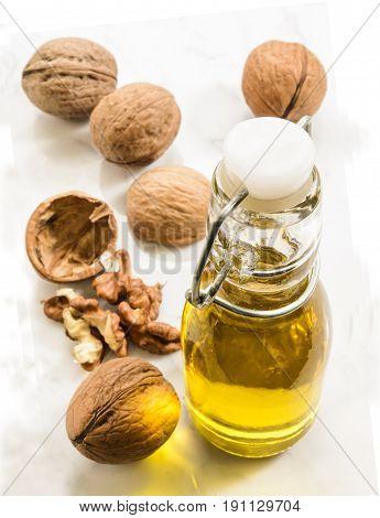 walnut oil in a bottle on bright marble