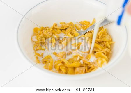 Pouring milk onto a bowl of sweetened cereal