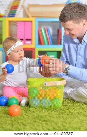 Father playing with his adorable little daughter in room with green carpet and blurred bookshelves on background