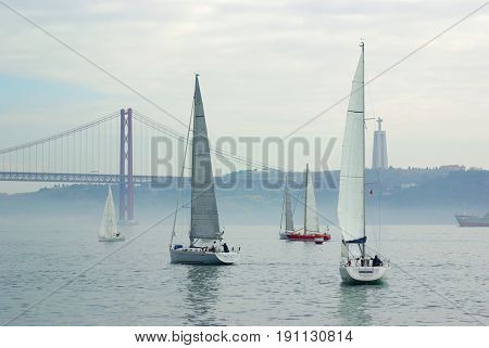 Boats sailing on the river Tagus with the 25 Abril bridge and the Cristo Rei in Lisbon, Portugal
