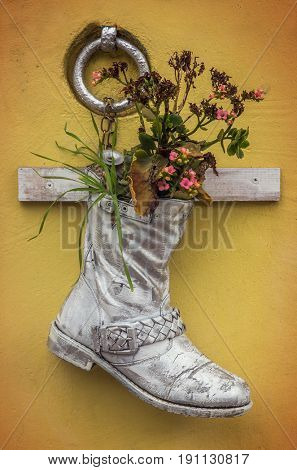 Old boot painted white with flowers hanged on a yellow wall