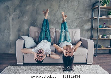 Funny Couple With Glasses Gesturing Is Lying Upside-down On The Sofa At Home. They Are So Cheerful,