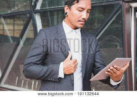 Businessman In Suit Holding Touch Pad While Standing Outside Building. Young Asian Male Using Digita