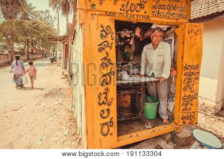 HALEBIDU, INDIA - FEB 22, 2017: Man working in small tailor store on street of indian city on February 22, 2017. Population of Karnataka state is 62,000,000 people