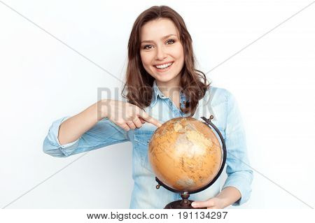 Young girl in denim shirt holding globe and pointing at it while smiling at camera on white.