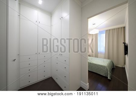 Dressing room of white high cabinets in a modern apartment