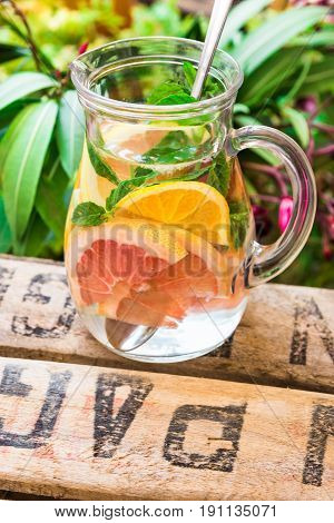 Detox infused citrus water in glass pitcher with oranges lemons grapefruits limes fresh mint on wood fruit garden box green plants and flowers outdoors summer refreshment