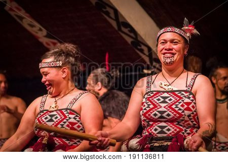 NORTH ISLAND, NEW ZEALAND- MAY 17, 2017: Close up of two Tamaki Maori ladies with traditionally tatooed face and wearing traditional dress at Maori Culture village holding a wooden sticks in Tamaki Cultural Village, Rotorua, New Zealand.