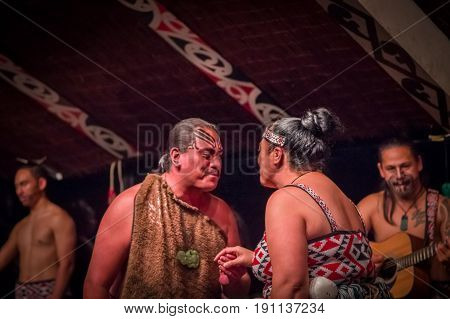 NORTH ISLAND, NEW ZEALAND- MAY 17, 2017: Tamaki Maori couple dancing with traditionally tatooed face in traditional dress at Maori Culture, Tamaki Cultural Village, in New Zealand.