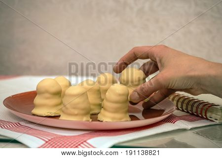 The confectioner puts out cookies. Popular in Israel confectionery made of cookies with cream - Crembo. Filed on a red round plate
