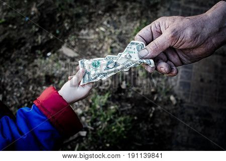 The child gives the money to a grown man. From hand to hand.