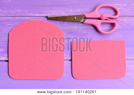 How to make a simple felt purse. Step. Quick and easy sewing crafts guide. Details cut from felt to create a purse. Scissors on wooden background. Top view