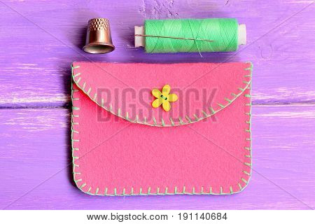 How to make a simple felt purse. Step. Sewing crafts tutorial. Handmade pink felt purse, thread, thimble on a wooden table. Top view