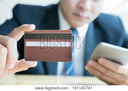 Male Holding A Credit Card And Using Smart Mobile Phone For Online Shopping. Businessman Purchase Go