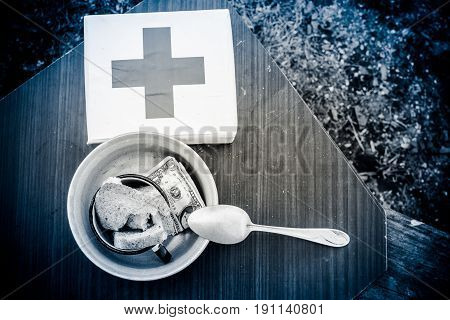 In a metal bowl are bread and money. Next is a box which shows a cross.