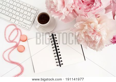 Office desk table with computer, cup of coffee and peony flowers. White wooden background. Coffee break, notes or plan writing concept. Top view, flat lay.