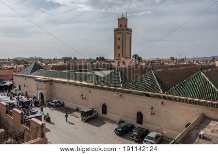 Marrakesh, Morocco - May 3, 2017: Roof and minaret of Mosque of Ben Youssef view from neighbors roof.