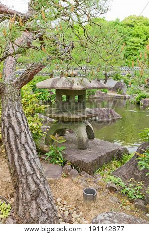 HIMEJI JAPAN - MAY 16 2017: Traditional stone lantern (toro) on the pond of Kokoen Garden near Himeji castle Japan. Garden was laid out in 1992 to commemorate 100 anniversary of Himeji city