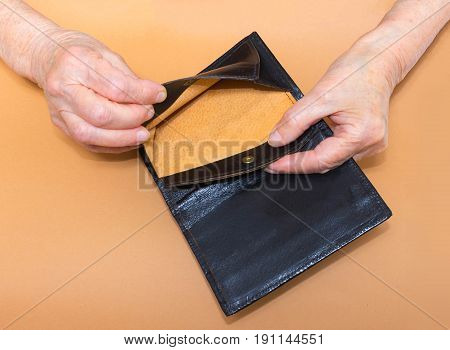 Senior woman sitting on window sill with empty purse, closeup. Poverty concept