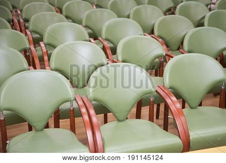 Group of empty the same chairs with modern backrest and green upholstery in rows at unknown auditorium