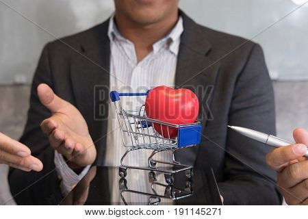 Businessman Showing Red Heart In A Blue Shopping Cart On Digital Tablet. Valentine's Day, Buying Lov