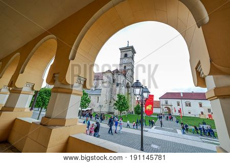 ALBA IULIA ROMANIA - APRIL 30 2017: Fish eye view with Saint Michael Roman Catholic Cathedral from under arcade of orthodox Coronation (Reunification) Cathedral in Alba Iulia city Transylvania Romania.