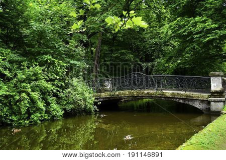 Old bridge across a canal on the grounds of Nymphenburg Palace Munich Germany.