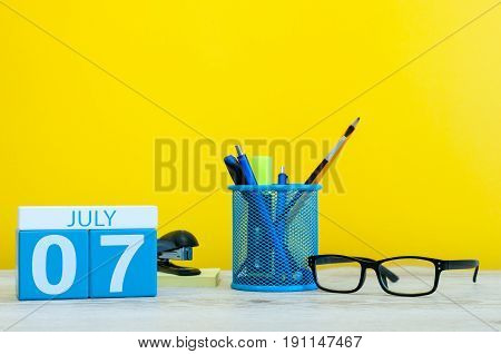 July 7th. Image of july 7, calendar on yellow background with office supplies. Summer time. With empty space for text.