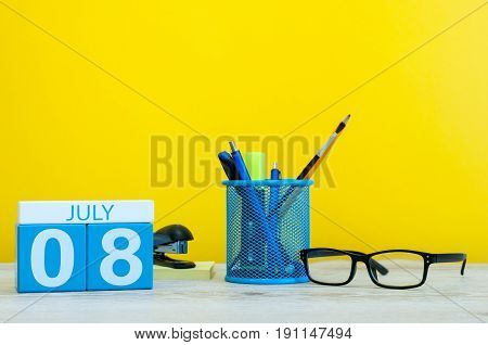 July 8th. Image of july 8, calendar on yellow background with office supplies. Summer time. With empty space for text.