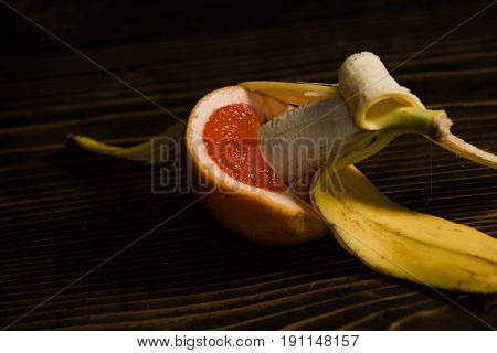 banana with yellow peel in red grapefruit on wooden background sex and sexual intercourse fruit love vitamin and dieting healthy food penis and vagina