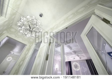 Doorway and ceiling with a ball-shaped chandelier in the hallway