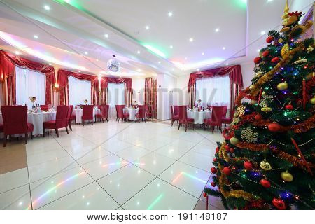 Beautiful banquet hall with served tables, red chairs, drapes and Christmas tree